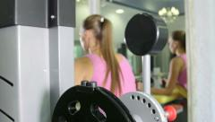 Stock Video Footage of Young fit woman doing hamstrings exercise on leg curl machine in fitness club