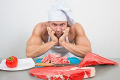 close-up of chef in a nightcap with huge pieces of meat on the table - stock photo