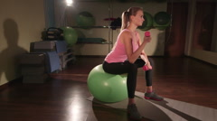 Fit young woman lifting light dumbbell on fitness ball in gym Stock Footage
