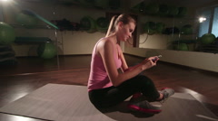 Woman using smartphone application to build custom routine in gym crane shot Stock Footage