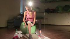 Fit woman wrapping injured knee using elastic bandage strap in gym Stock Footage