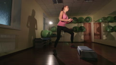 JIB CRANE: Fit young woman doing step aerobics exercise in fitness club Stock Footage