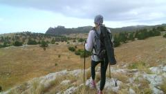 Day hiking woman standing on edge of cliff at plateau mountain peak Stock Footage