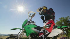 Young enduro racer in motorcycle protective gear on dirt bike against sun Stock Footage
