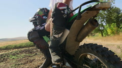 Motocross rider boy with his dirt bike looks afar Stock Footage