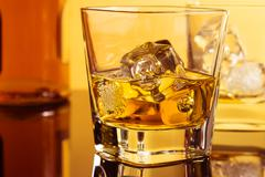 Close-up of two glasses of whiskey near bottle on table with reflection, warm Stock Photos