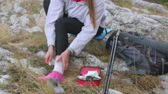 Woman hiker injured while hiking in mountains applying ankle bandage Stock Footage