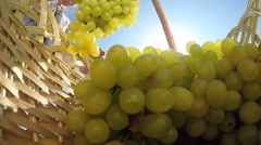 Senior woman carrying basket with seedless kishmish white grapes Stock Footage