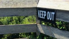 "Slow Steady Pan Across Wooden Fence to Reveal a ""KEEP OUT"" Sign Stock Footage"