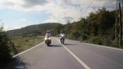 Two scooter riders drive on contry road, front view Stock Footage