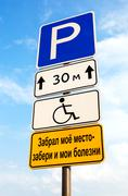 Handicapped parking sign against blue sky. Text in Russian: Took my place - a - stock photo