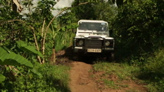 A Landrover drives down a dirt track in rural Uganda, Africa Stock Footage