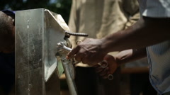 Two African men maintaining a water well in rural Uganda, Africa - stock footage