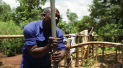 An African man handling a plastic tube used to install a new well - stock footage