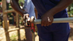 An African man threading a plastic tube used to install a new well - stock footage