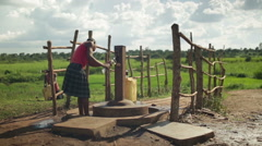 A young African girl fills a water container by a water pump Stock Footage