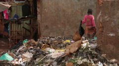 Young African child looking through a rubbish pit in a slum Stock Footage