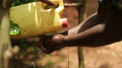 An African lady using a handwash station made from plastic containers Stock Footage