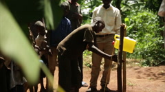 An African child using a handwash station made from plastic containers Stock Footage