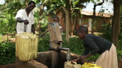 An African boy filling up yellow water containers at a well Stock Footage