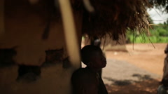 Two African boys sheltering from the heat outside a mud hut - stock footage