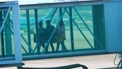 Passengers walking down the docking sleeve's ramp Stock Footage