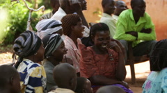 African ladies sitting and laughing at a community meeting in Uganda Stock Footage