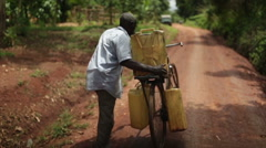 African man using a bicycle to collect water in 3 containers pushing bike Stock Footage