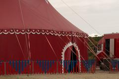 Big red top circus tent on a field in a park, - stock photo