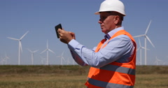 Modern Technology Engineer Examining Tablet Electricity Production Wind Turbines Stock Footage