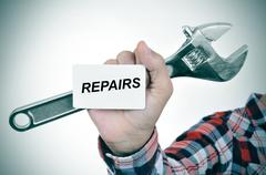 Man with an adjustable wrench and a signboard with text repairs Stock Photos