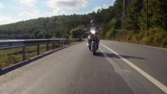 Young man wearing a suite rides a scooter on country road, front view - stock footage
