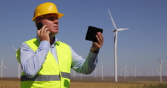 Wind Turbines Engineer Use Mobile Phone Touch Tablet Contact Maintenance Team Stock Footage