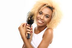 Dark skinned young woman combs her hair brush Stock Photos