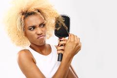 Dark skinned young woman combs her hair brush - stock photo