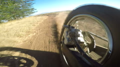 Enduro racer riding bike on dirt track kicking up dust rear wheel point of view Stock Footage
