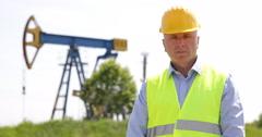 Russian Field Oil Pump Farm Engineer Man Job Looking Camera Gasshopper Pumpjack Stock Footage