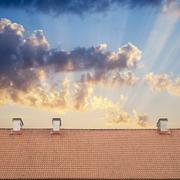 cloudy blue sky and tiled roof top - stock photo
