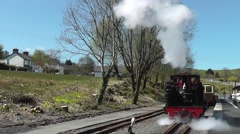 Steam train engine setting off from the station Stock Footage