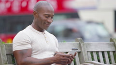4K Portrait of casual smiling man sitting on park bench with mobile phone Stock Footage