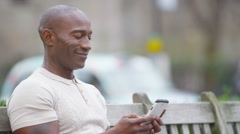 4K Portrait of casual smiling man sitting on park bench with mobile phone - stock footage