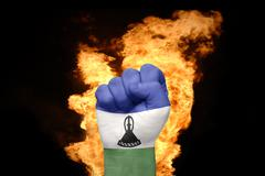 Fire fist with the national flag of lesotho Stock Photos