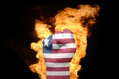 Fire fist with the national flag of liberia Stock Photos