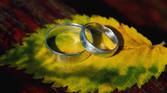 Two wedding rings on a yellow sheet Stock Footage