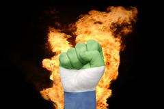 Fire fist with the national flag of sierra leone Stock Photos