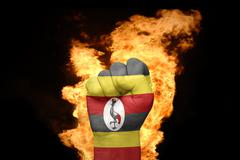 Fire fist with the national flag of uganda Stock Photos