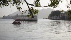 Tourist boat passing in front of Udaipur lake palace Stock Footage