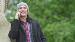 4K Portrait of casual smiling man making mobile phone call outdoors in the city Stock Footage