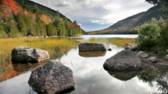 Rocks and relfections in still fall lake in acadia national park Stock Footage