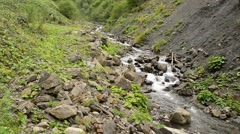 Water stream in mountains flows between rocky hills in summer Stock Footage